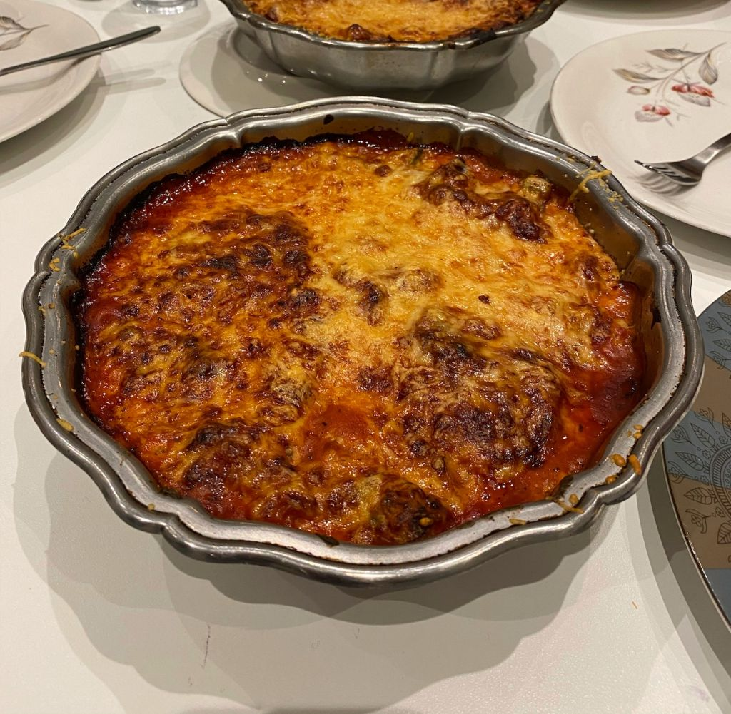 Selbstgekochte Lasagne in einer silbernen Form auf einem weißen Tischtuch.
