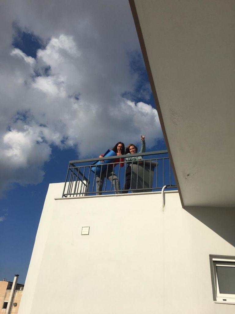 Meine Mitbewohnerin Tine und ich wie wir auf der Dachterasse stehen mit unseren Sportmatten in der Hand.