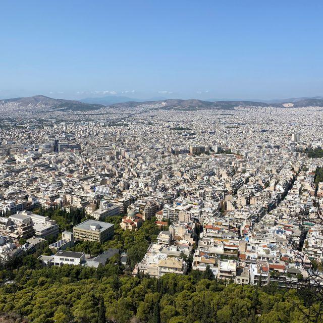 Das Bild zeigt den Ausblick über Athen. Im vorderen Teil des Bildes sind viele Bäume zu sehen. Das Stadt-Panorama ist von einer kleinen Berglandschaft umgeben.