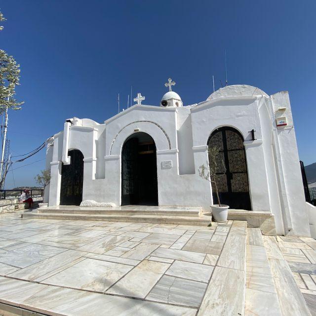 Im Vordergrund ist der helle Marmorboden der Bergspitze zu sehen. Im Hintergrund befindet sich die weiße Sankt-Georgs-Kapelle.