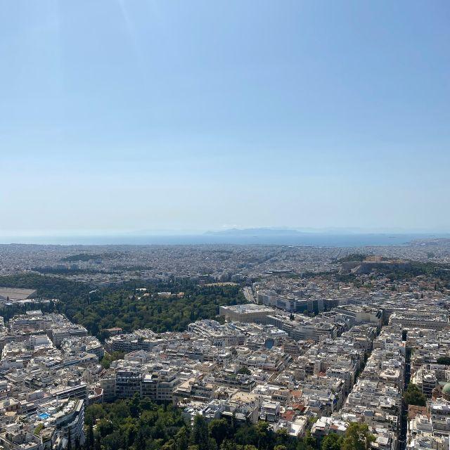 Ein Foto des Stadtpanoramas von der Bergspitze aus. Neben den Grünflächen sind auch Häuserreihen, die Akropolis und sogar das Meer in der Ferne zu sehen.