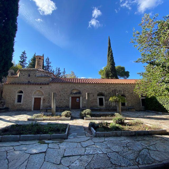 Bei strahlend blauem Himmel und zwischen ein paar Bäumen ist das Kloster Kesariani zu sehen. Das alte Kloster nimmt fast das gesamte Bild ein. Im Vordergrund sind bepflanzte kleine Grünflächen zu erkennen.