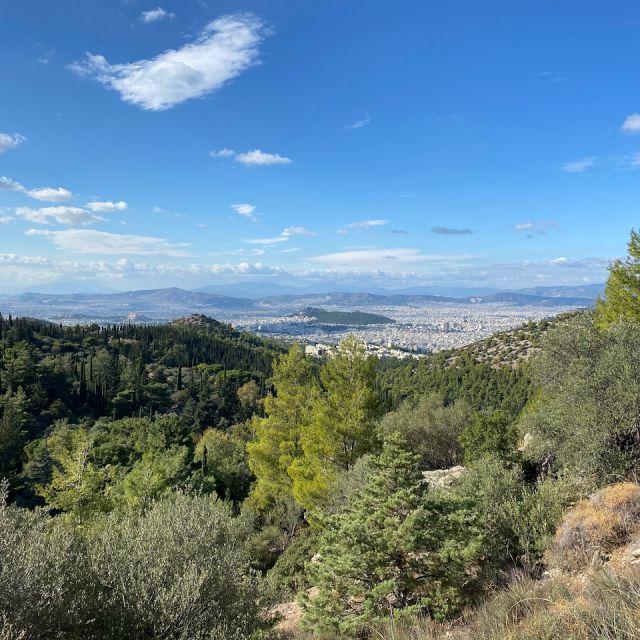Das Foto von der Aussicht des Bergs Hymettos zeigt im Vordergrund hauptsächlich die grüne Berglandschaft. Im Hintergrund ist die Stadt Athen nur ganz weit in der Ferne zu erkennen.