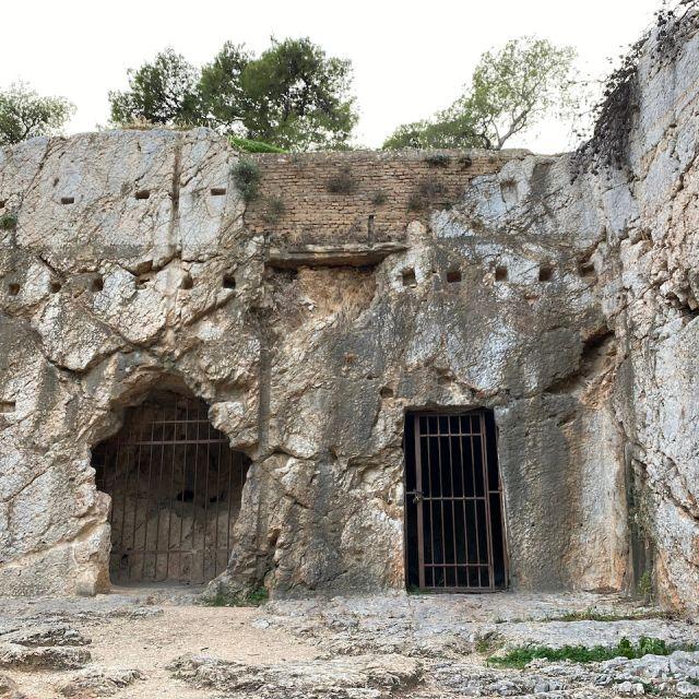 Die Sicht auf das Gestein des Filopapposhügel, in welchem sich zwei Löcher mit Gitterstäben befinden. Es handelt sich um Gefängniszellen im Gestein.