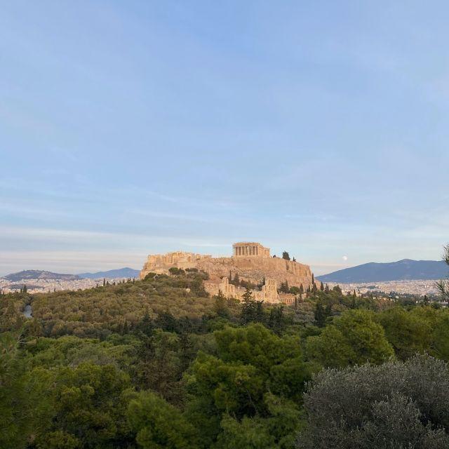 In der Mitte des Bildes befindet sich die Akropolis, umgeben von einer grünen Waldlandschaft.