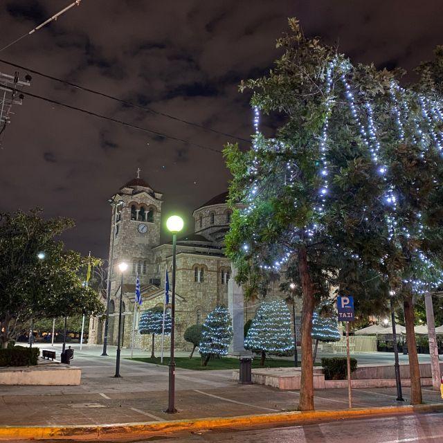 Im Vordergrund stehen zwei mit Lichtern geschmückte Bäume, während im Hintergrund eine Kirche zu sehen ist. Das Bild wurde in der Dunkelheit mit einer Langzeitbelichtung aufgenommen.