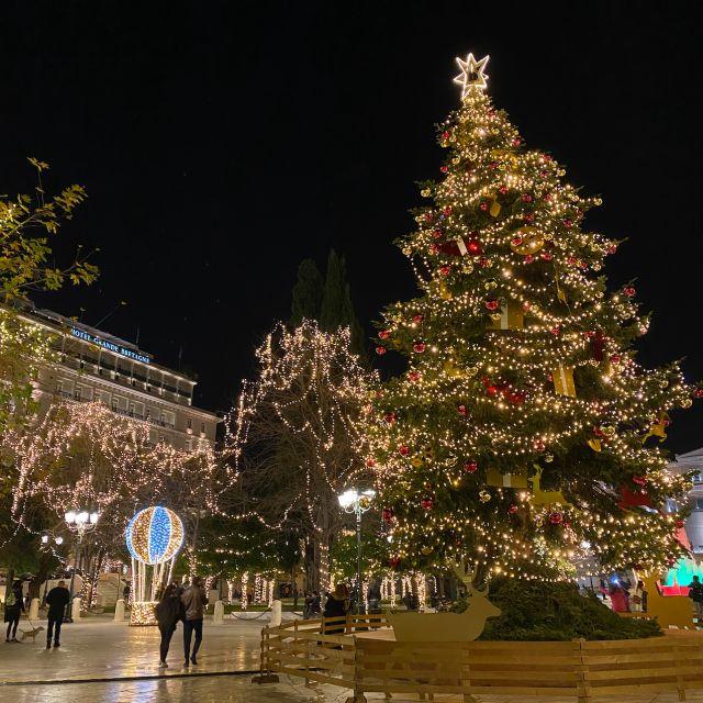 Zu sehen ist der große Weihnachtsbaum auf dem Syntagma-Platz. Er ist mit gelben Lichtern, roten Kugeln und einem Stern an der Spitze geschmückt. Im Hintergrund sind weitere geschmückte Bäume und Menschen zu sehen.