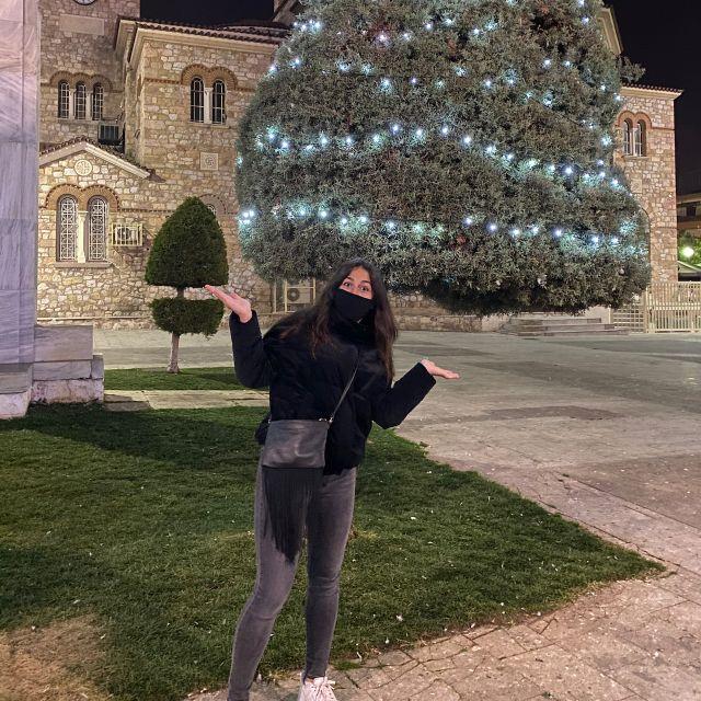 Im Vordergrund stehe ich mit angehobenen Händen, die auf den mit Lichtern geschmückten Baum im Hintergrund zeigen. Ich trage eine schwarze Jacke und Maske und eine graue Hose. Hinter dem Baum ist ein Teil einer Kirche zu sehen.