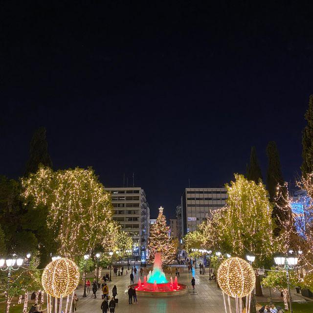 Zu sehen ist der Syntagmaplatz in Athen. Dort steh ein kleiner bunter Brunnen mit Lichtern, geschmückte Bäume und ein großer aufgestellter Weihnachtsbaum.