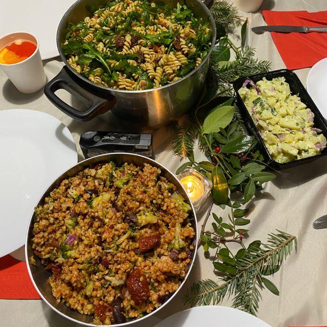 Das Foto wurde von oben aufgenommen und zeigt einen gedeckten Tisch mit roten Servietten, Nudelsalat, Bulgursalat und Kartoffelsalat.