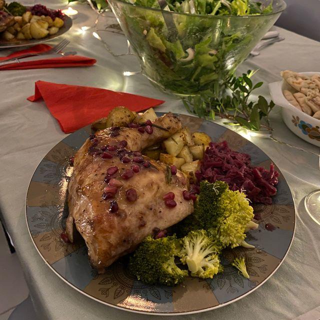 Zu sehen ist ein gefüllter Teller mit Hühnchen in einer Granatapfelsoße und mit Brokkoli und Kartoffeln als Beilage. Im Hintergrund steht eine Schüssel mit grünem Salat und weitere gefüllte Teller.