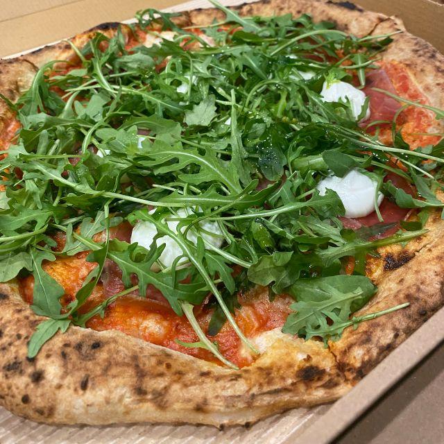 Zu sehen ist eine Nahaufnahme von einer Rucola Pizza mit Mozzarella.