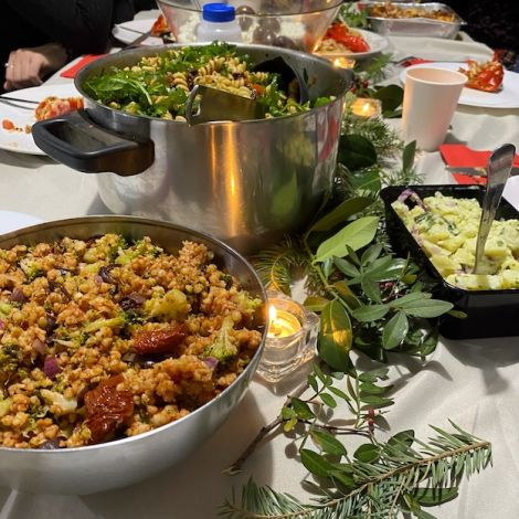 Ein gedeckter Tisch mit Weihnachtsdekoration, einer Kerze und drei verschiedenen Salaten.