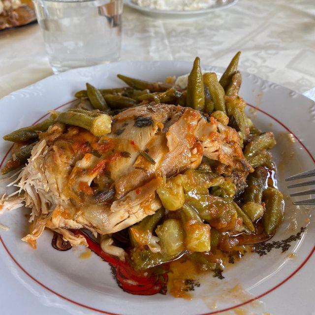Zu sehen ist ein gefüllter Teller mit Okraschoten und Hähnchen in einer Tomatensoße.