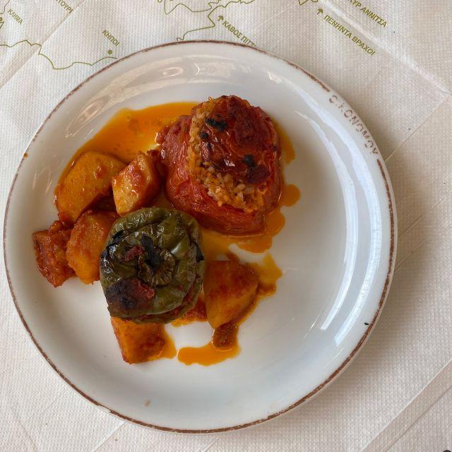 Ein weißer Teller mit Kartoffeln und mit Reis gefüllten Paprikas auf einem Tisch.