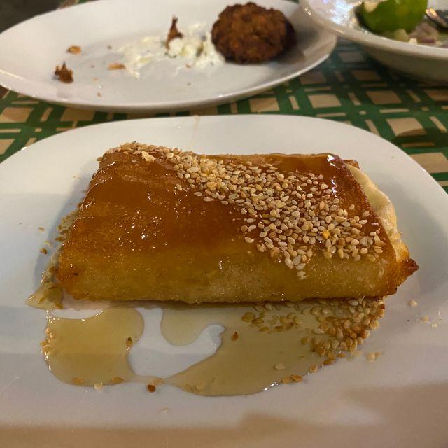 Eine Nahaufnahme von überbackenem Fetakäse mit Honig und Sesam. Im Hintergrund ist ein weiterer Teller mit Zucchini Frikadellen auf dem Tisch zu sehen.