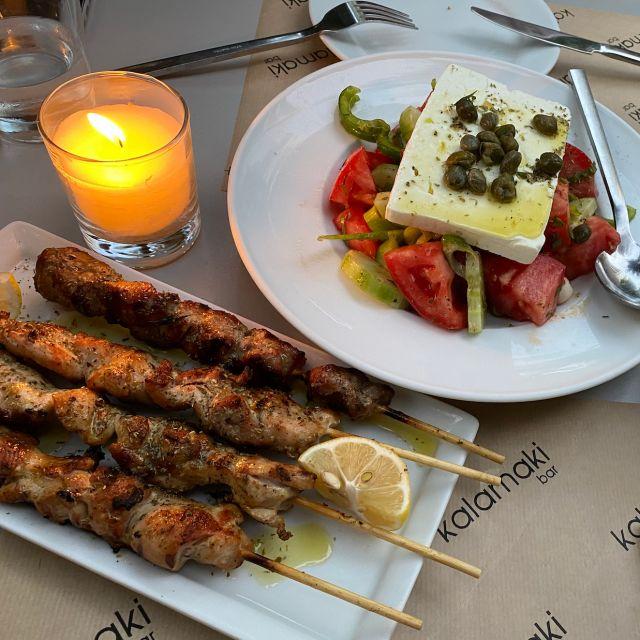 Ein Tisch mit zwei Tellern und einer brennenden Kerze. Ein Teller ist gefüllt kit Souvlaki-Spießen und der andere mit einem griechischen Bauernsalat.