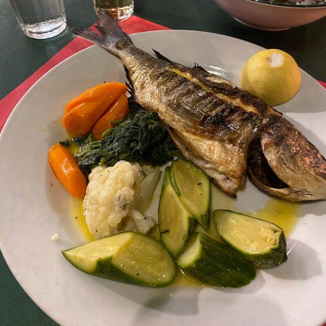 Ein weißer Teller mit einer gegrillten Dorade, gekochtem Blumenkohl, Zucchini, Brokkoli und Karotten. Am Tellerrand befindet sich eine Scheibe Zitrone.