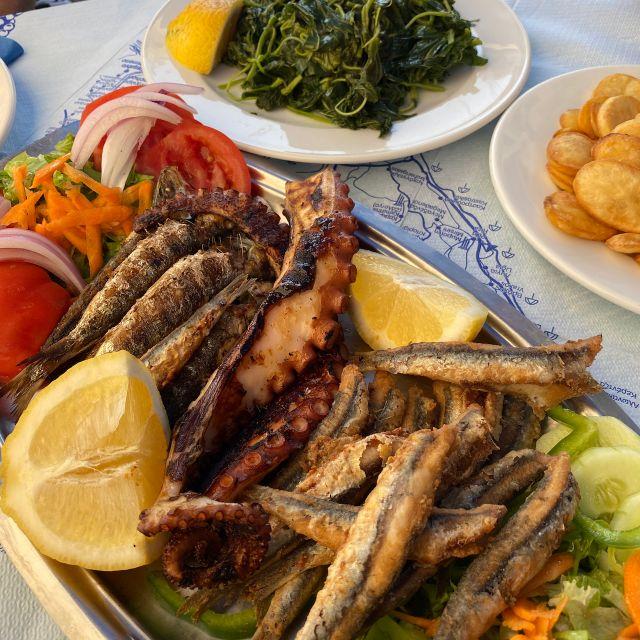 Drei Teller gefüllt mit einem Wildkräutersalat, Pommes, Sardellen und Tintenfisch.