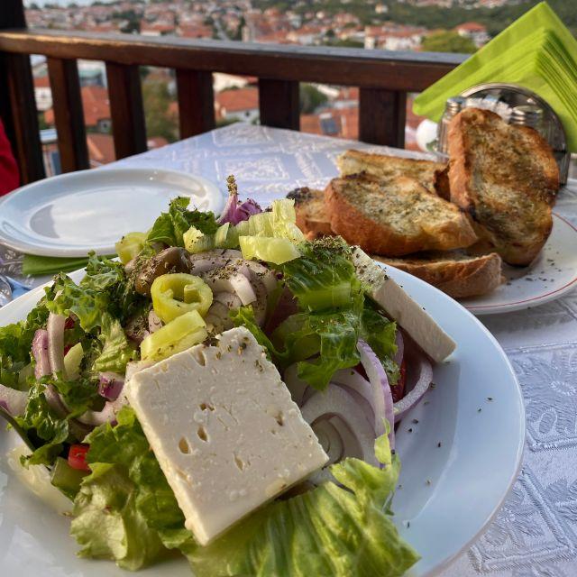 Im Vordergrund befinden sich zwei Teller, gefüllt mit griechischem Salat und Knoblauchbrot. Das Foto wurde in einem Restaurant mit Aussicht auf eine Wohnsiedlung aufgenommen.