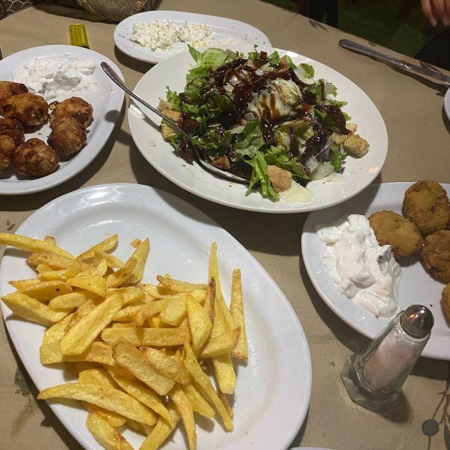 Ein Tisch gefüllt mit verschiedenen Vorspeisen. Zucchini-Frikadellen, Pommes, einen Salat, Tomaten-Frikadellen und Tirokafteri.