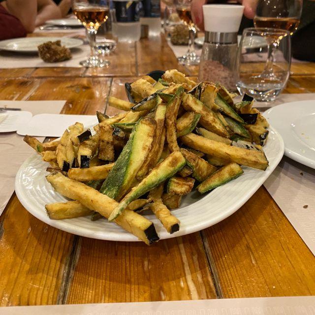 Auf einem Holztisch steht ein Teller mit frittierten Auberginen und Zucchini. Im Hintergrund sind gefüllte Gläser und leere Teller zu sehen.