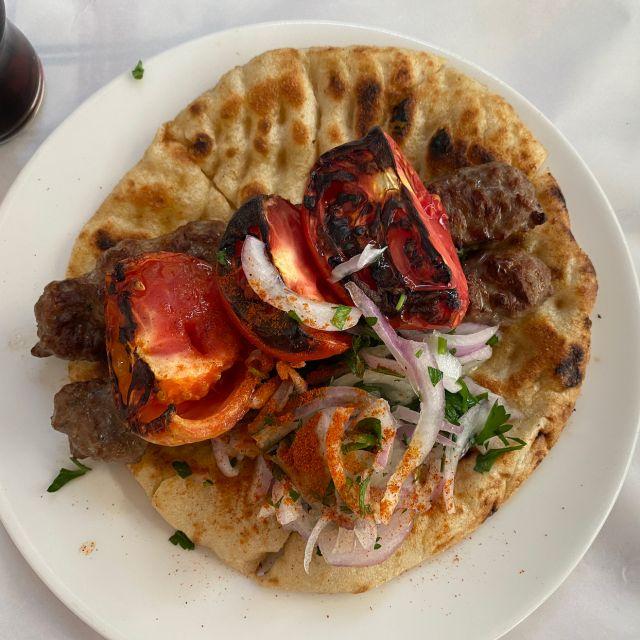 Eine Nahaufnahme von einem von oben fotografierten Teller. Auf dem Teller befindet sich ein Pita-Brot, zwei Hackfleisch-Spieße, Zwiebeln und Tomaten.