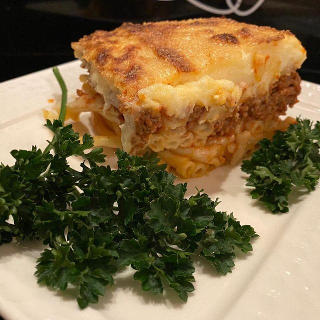 Ein Stück Pastitsio serviert auf einem weißen Teller mit Petersilie.