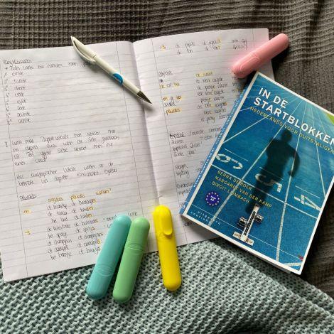 Man sieht ein aufgeschlagenes Vokabelheft und ein Buch zum Thema Niederländisch-Lernen. Außerdem erkennt man Textmarker.