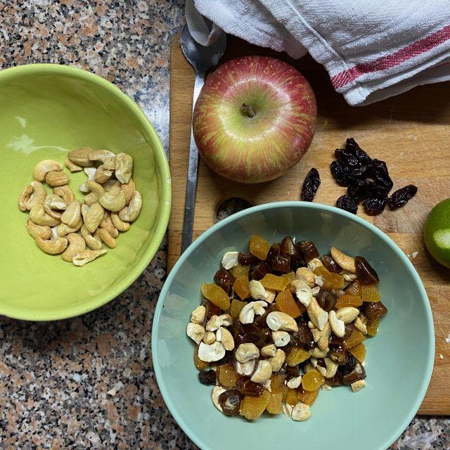 Klein geschnittene Trockenfrüchte und zerhackte Nüsse befinden sich in einer kleinen Schüssel.