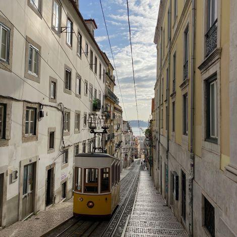 Eine Straßenbahn fährt durch eine enge Gasse Lissabons, im Hintergrund ist der Rio Tejo zu erkennen