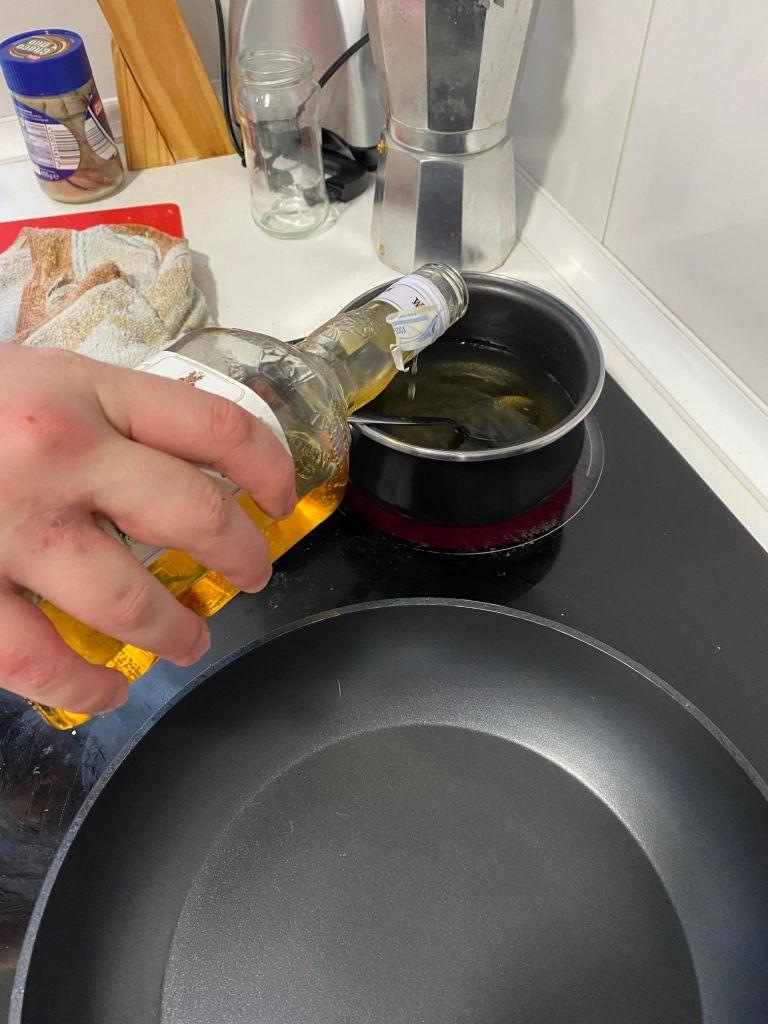 Eine Hand kippt Whisky aus einer Flasche in einen Topf auf dem Ceranfeld.