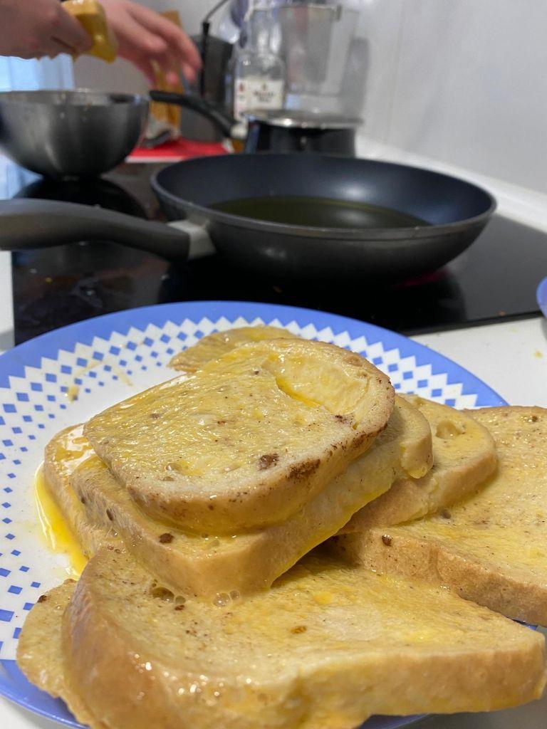 Toastscheiben auf einem Teller von Ei durchtränkt, im Hintergrund ein Ceranfeld mit Pfanne.