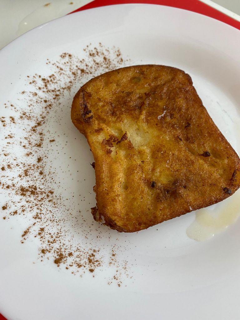 Eine braungebrannte Torrija auf weißem Teller, drumherum etwas Zimt verstreut.