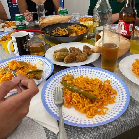 Tisch mit Reisgericht, Kroketten, Bier, Gläsern und Tassen.