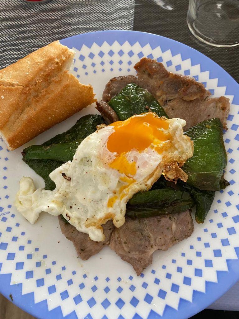 Schweinefleisch, grüne Paprika, Rührei und Weißbrot auf einem Teller.