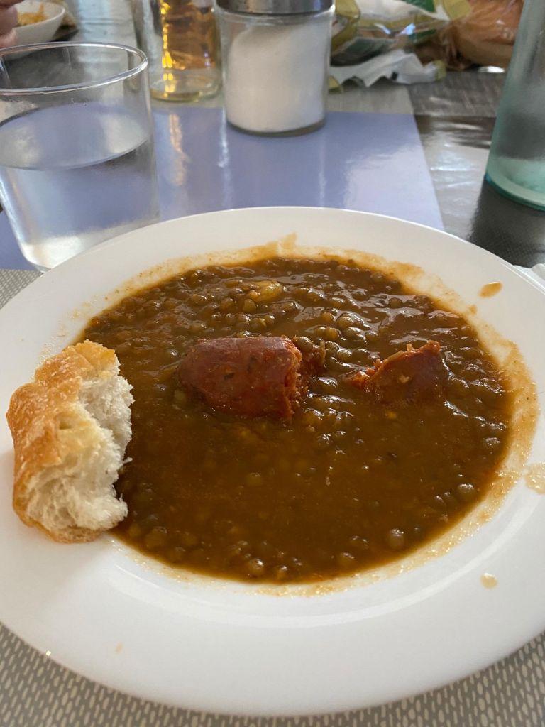 Teller mit braunen Linsen und einer Paprikawurst, am Rand ein Stück Weißbrot.