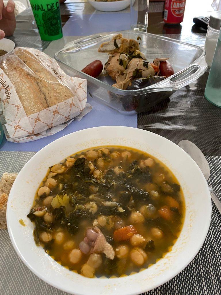 Teller mit Kichererbsen und Blattspinat, im Hintergrund eine Glasschüssel mit Hähnchenschenkeln und ein Laib Brot.