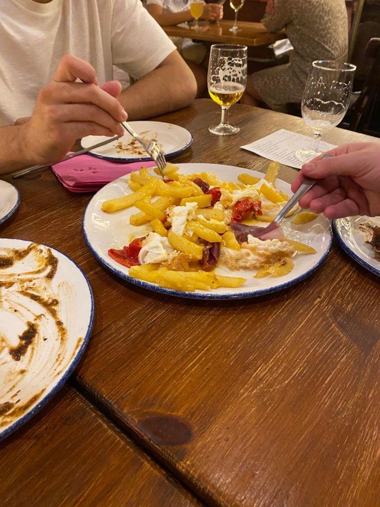 Teller mit Rührei, Pommes, roter Paprika und Bacon.