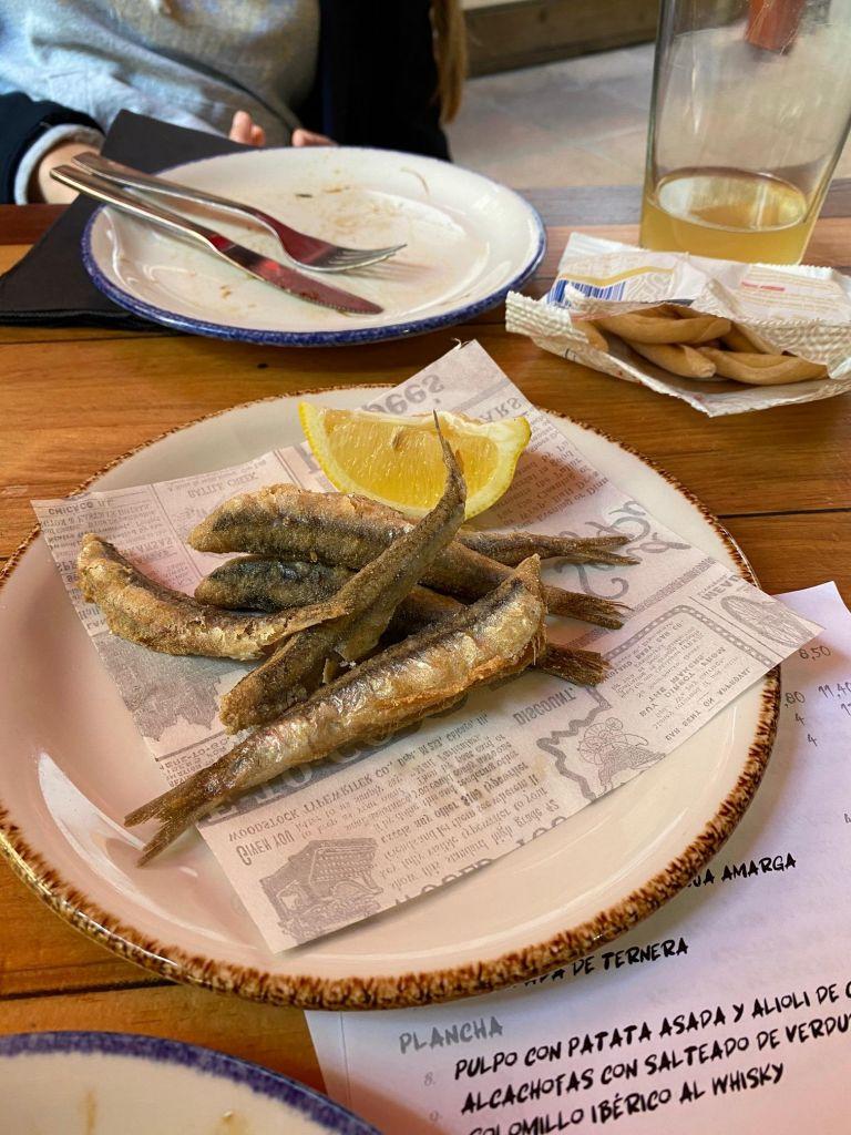 Panierte Sardellen auf einem Teller mit Zitronenspliss, im Hintergrund eine offene Tüte mit kleinen Bananenförmigen Brotstücken.