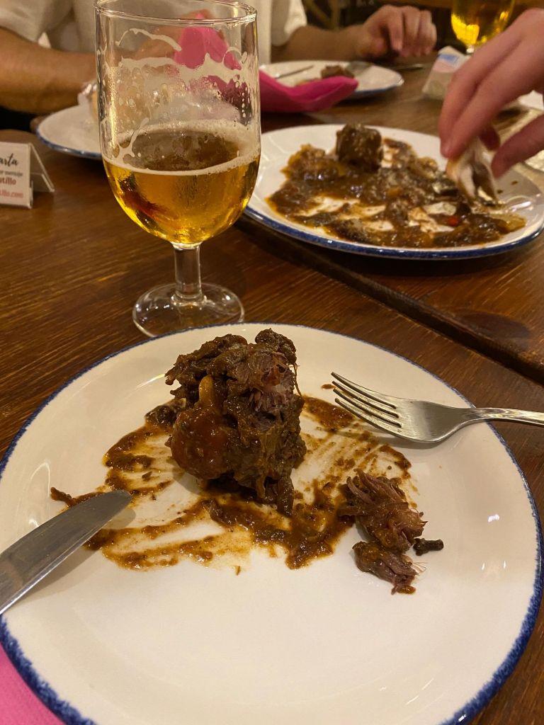 Ein Stück Stierschwanz mit Knochen in brauner Soße auf einem Teller.