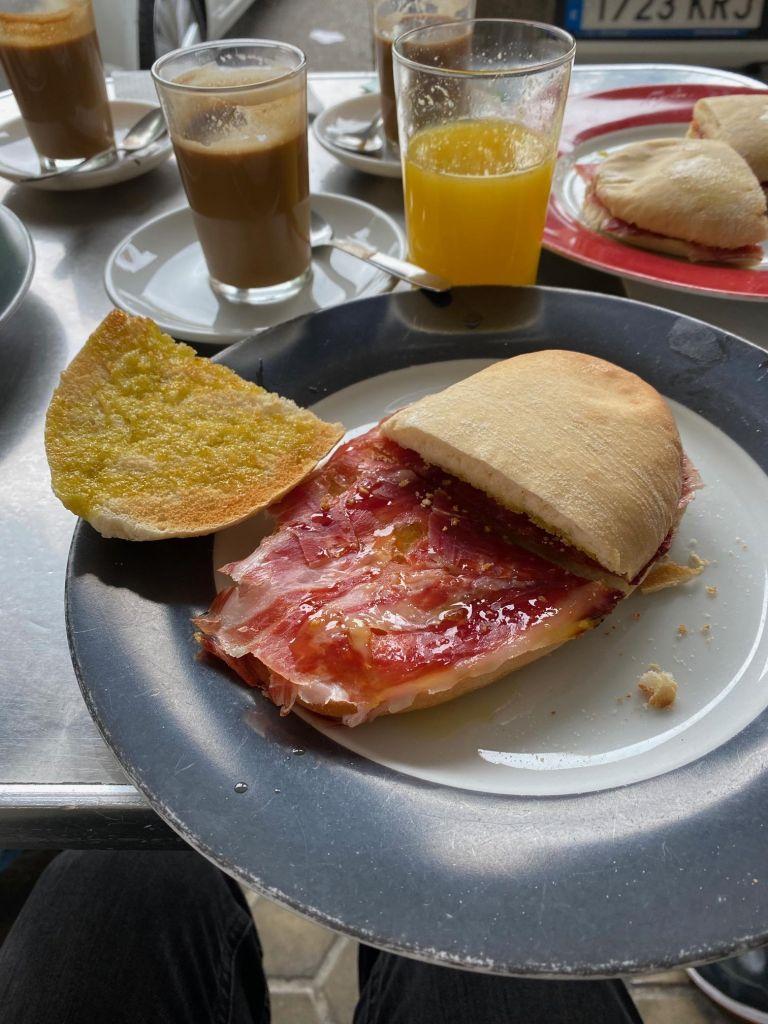 Brot mit rotem Schinken, im Hintergrund ein Glas Milchkaffee und ein Glas Orangensaft.