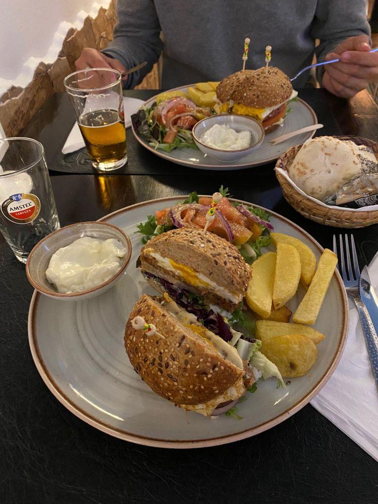 Halbierter Burger mit Pommes, Salat, weißer Soße auf einem Teller.