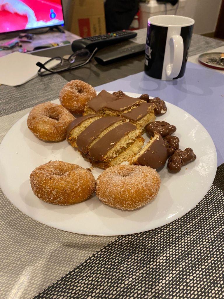 Teller mit Donuts und Schokoladengebäck und mit Schokolade überzogenen Nüssen.