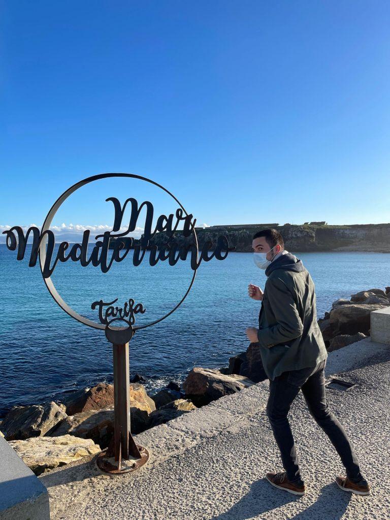 """Junger Mann mit Maske neben einem Schild """"Oceano Mediterraneo"""" in Läuferstellung."""