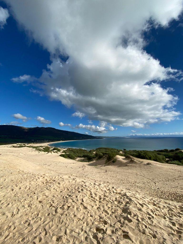 Sanddüne mit Strand und Bergen.