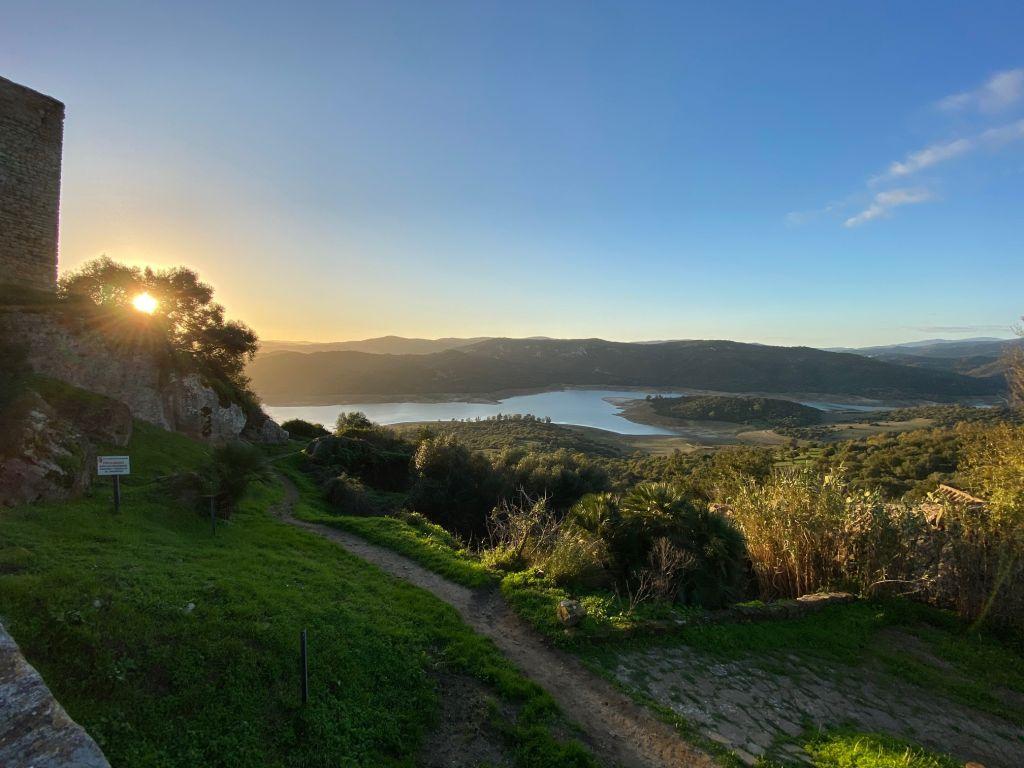 See mit Halbinsel und Bergen im Hintergrund vor untergehender Sonne.