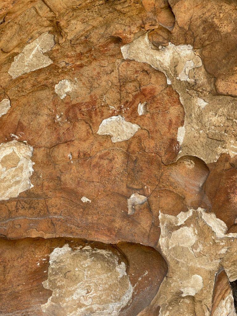 Eine Steinwand, auf der man die Umrisse eines roten Stierähnlichen Wesens erkennt; an manchen Stellen ist der Stein abgebröckelt.