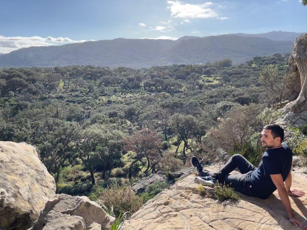 Junger Mann sitzt auf dem Berg vor einem Panorama aus Bäumen und Bergen am Horizont.