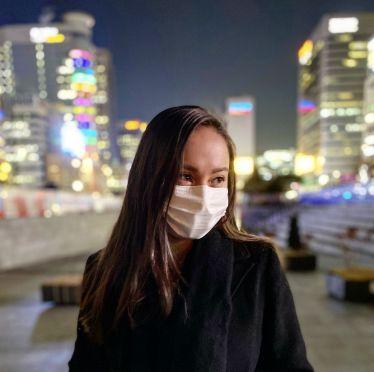 Frontalaufnahme vor vielen beleuchteten Gebäuden in der Nacht